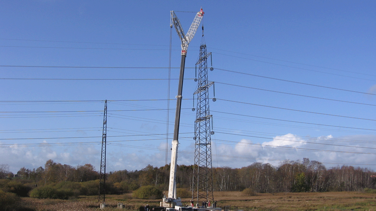Relocation of a 400 kV overhead transmission line tower to a new foundation. A big mobile crane relocates the whole tower while the conductors and the ground wires are installed