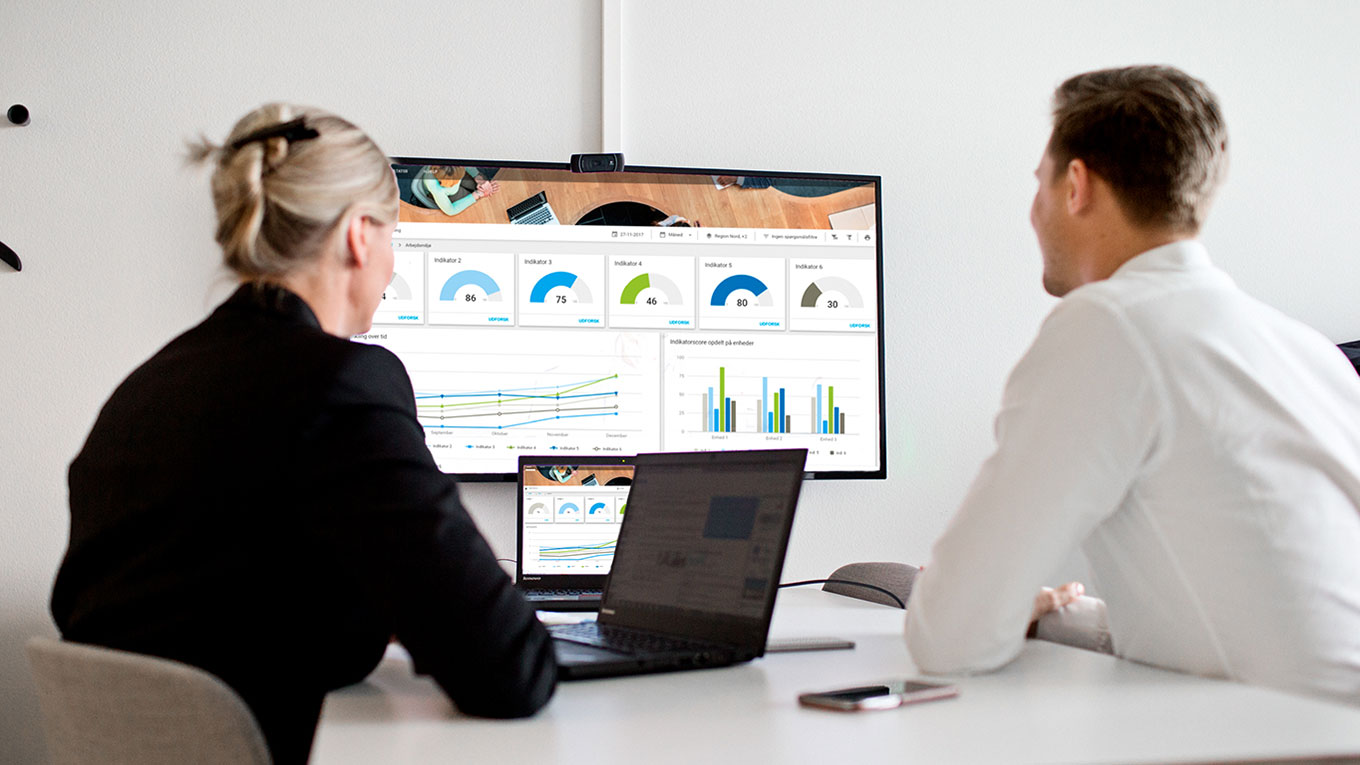 Two people in meeting looking at screen with graphs, charts and diagrammes