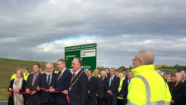 (c)Ramboll. Official opening of the A31 Magherafelt on the morning of 6 October, 2016. Chris Hazzard, Infrastructure Minister (with scissors). To his right are Francie Molloy, MP for Mid Ulster, and Conor Loughery, Transport NI Western Divisional Manager. To his right is Trevor Wilson, Chair of Mid Ulster Council.