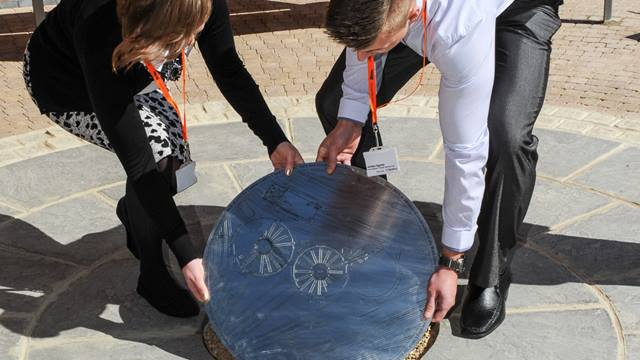 Kate Mallender  Apprentices laying the plaque in the paving to mark the centre of Roundhouse 2 being safely preserved below