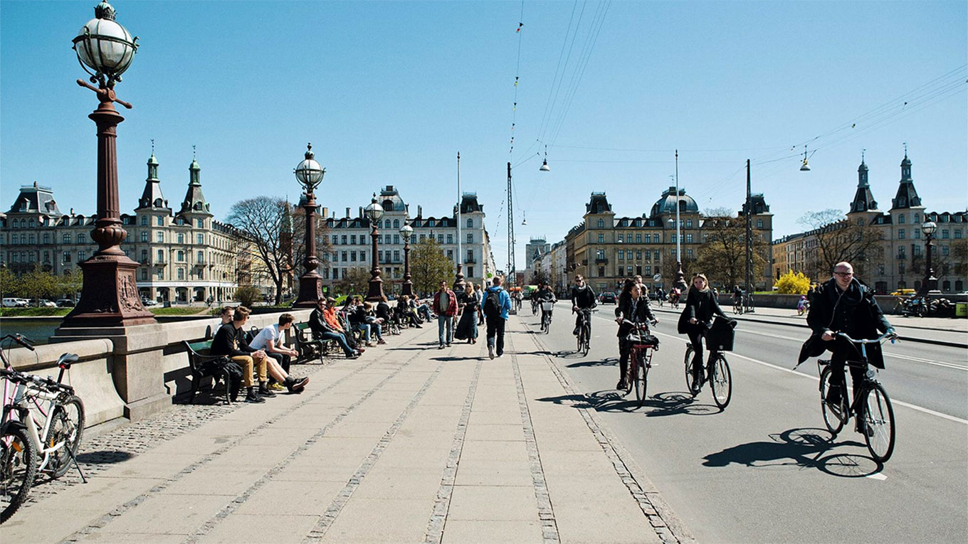 Cyclists and people on benches on Dronning Louises Bridge in Copenhagen