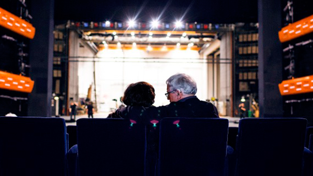 Old couple embracing each other in the theatre